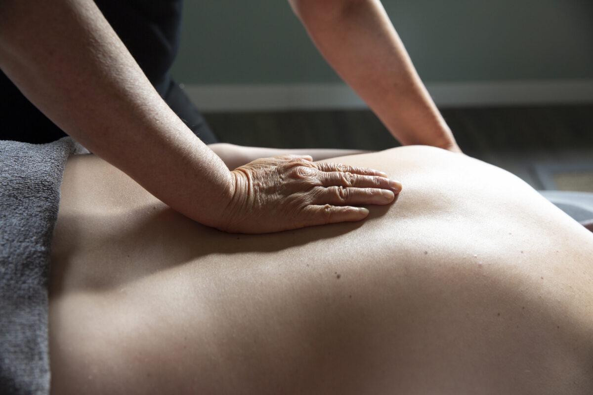 Beeld van Mandy van der Ploeg die massagetherapie geeft; met aandacht wordt de rug van een man gemasseerd.