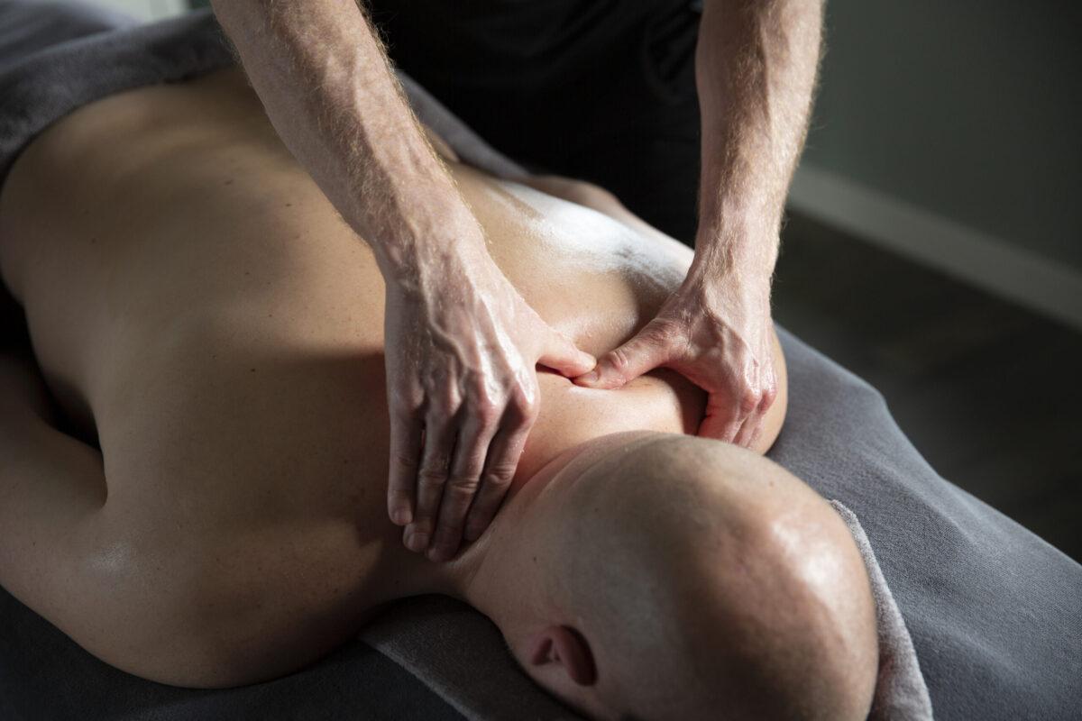 Foto waar holistisch masseur Eric zijn duimen gebruikt om spierknoop in schoudergebied los te masseren bij een man.