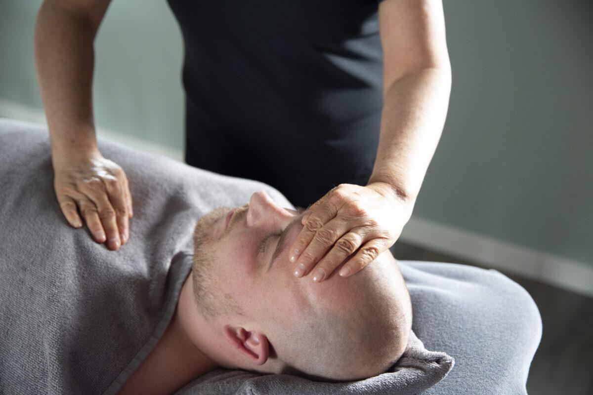 Beeld van chakramassage waar de masseur een hand legt op hart chakra en voorhoofd chakra bij de man op de massagetafel.