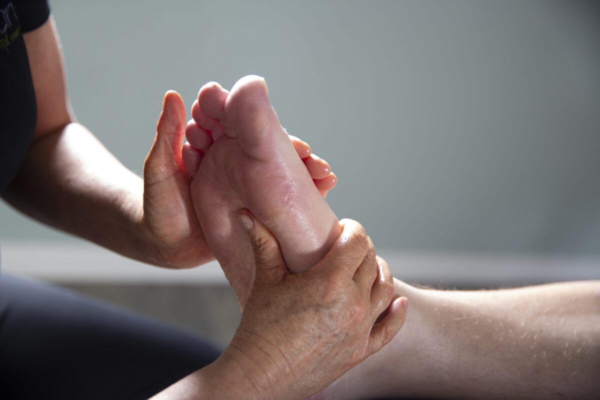 Foto van een voetreflexmassage; duim masseur op zonnevlecht onder voet.