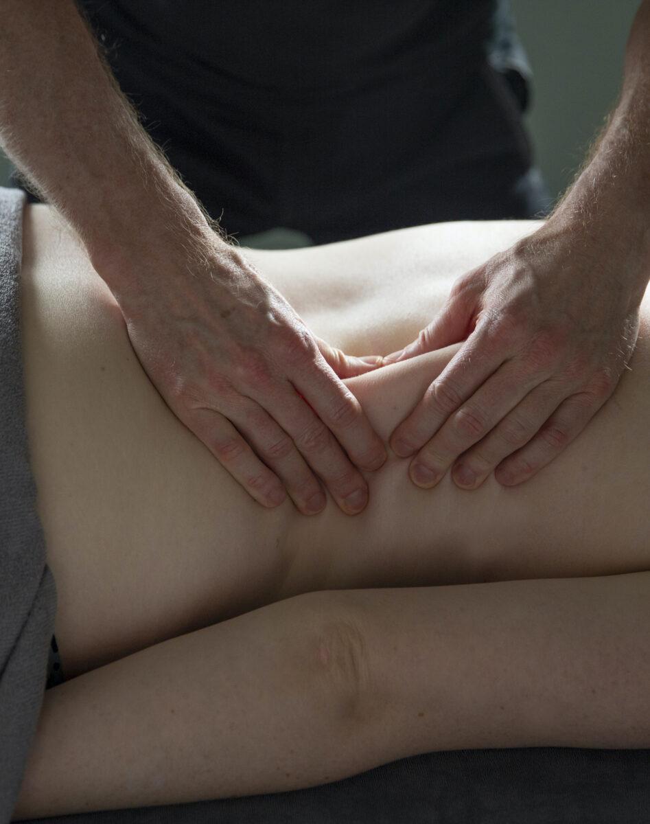 Beeld van een bindweefselmassage, masseur Eric van der Ploeg pakt huidplooi op en rolt deze uit.