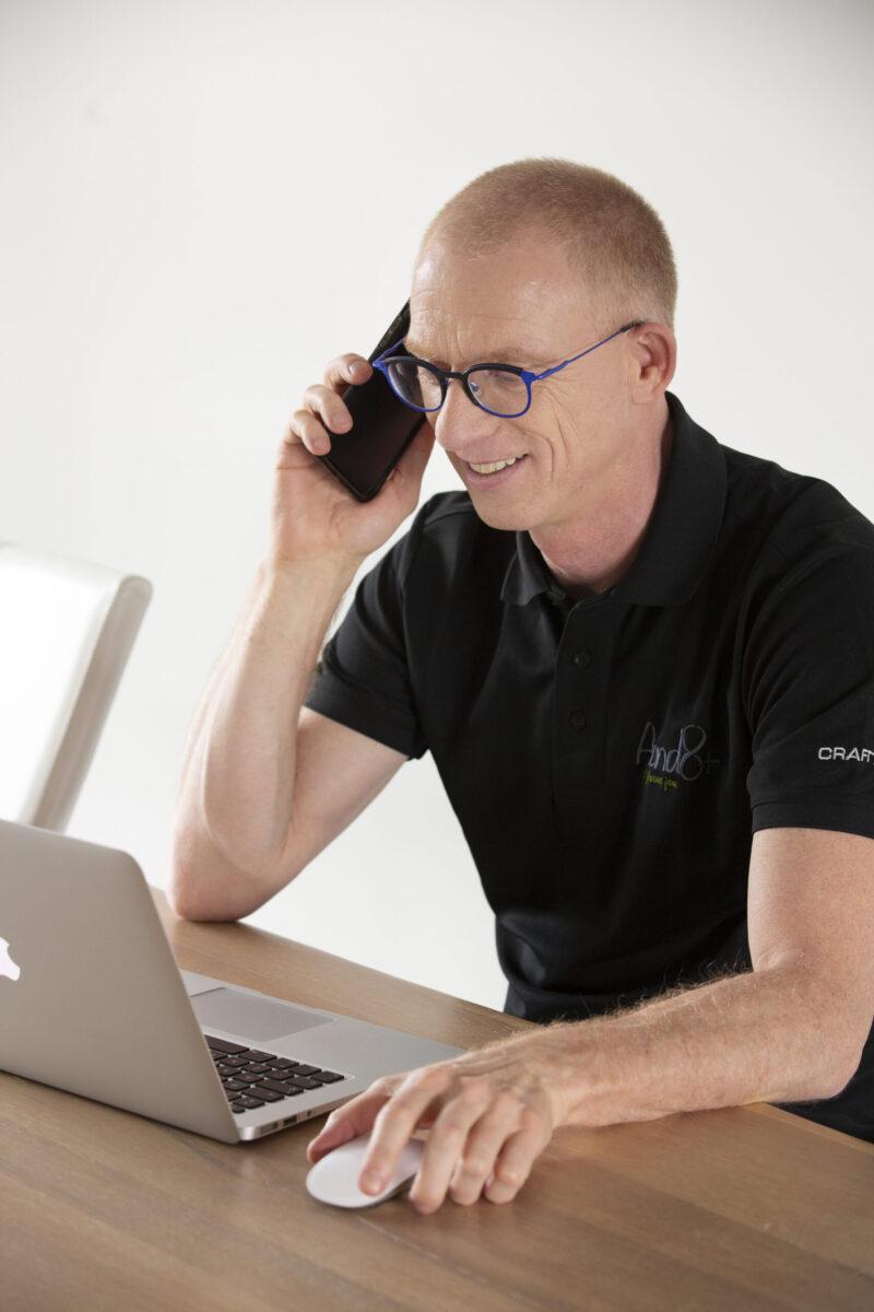 Foto van Eric achter computerscherm, met telefoon in de hand; neem contact op met ons als onze aanpak je wat lijkt.