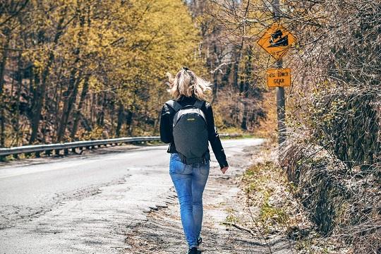 Vrouw met rugzak die besluit te gaan lopen op haar pad...