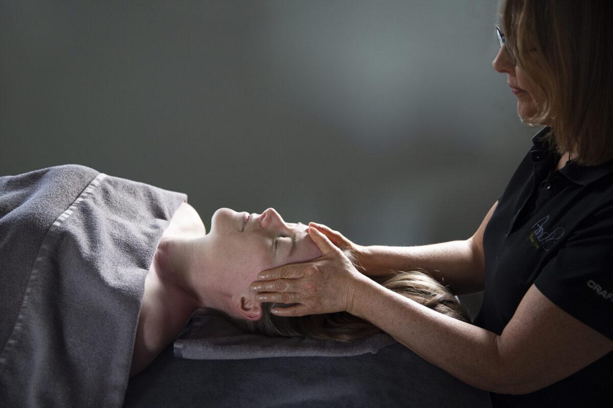 Beeld van energetische massage van het hoofd waarbij de masseur het hoofd van de cliënt aanraakt.